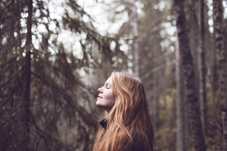 Tyttö metsässä silmät kiinni.