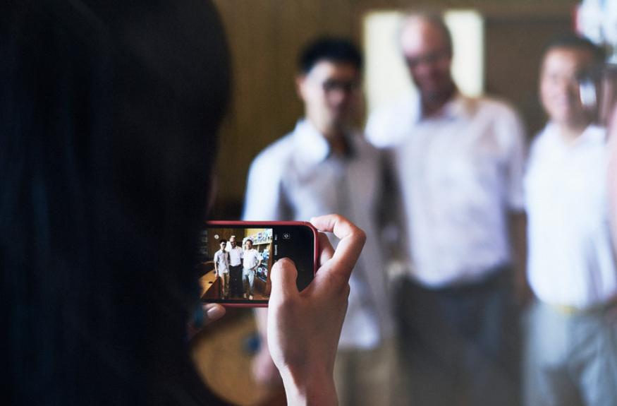 Kolme ihmistä kuvassa ja valokuvaaja.