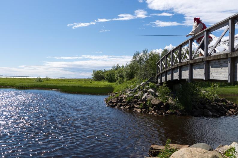Joulupukki kalastaa sillalla